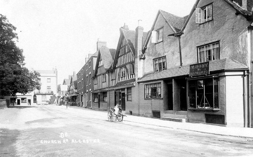 A view looking along Church Road (now street), Alcester. A hand cart and milk churn are standing on the roadside. 1910s. |  IMAGE LOCATION: (Warwickshire Museums. Photographic Collections.)