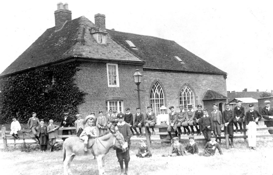A group of boys and masters outside The Old Grammar School, Alcester.  The headmaster, Mr. W. Parvin is leaning on the fence on the extreme right and the assistant headmaster is 5th from the left. The child on the donkey is the headmasters son.  1890s |  IMAGE LOCATION: (Warwickshire Museums. Photographic Collections.)