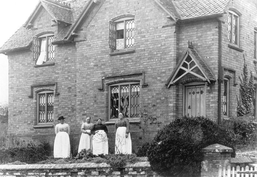 Estate houses with four women in long white aprons standing in front. Alscot Park, Preston on Stour.  1882 |  IMAGE LOCATION: (Warwickshire Museums. Photographic Collections.)
