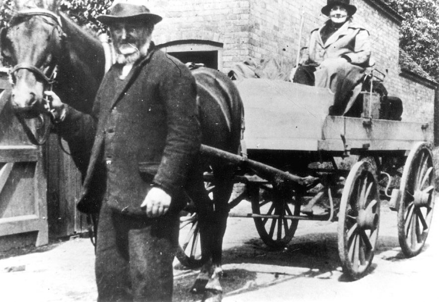 Mr. Thomas Walton, village carrier, with his horse and cart in Preston on Stour. He was the carrier from 1852 to 1936 when this photo was taken.  1936 [The lady in the cart is thought to be Esther Walton, who married Thomas in later life] |  IMAGE LOCATION: (Warwickshire Museums. Photographic Collections.) PEOPLE IN PHOTO: Watton, Thomas, Watton as a surname