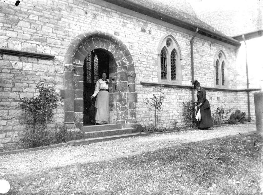 Newbold Pacey parish church.  Lady standing in door archway, another lady nearby.  1900s    IMAGE LOCATION: (Warwickshire Museums. Photographic Collections.)