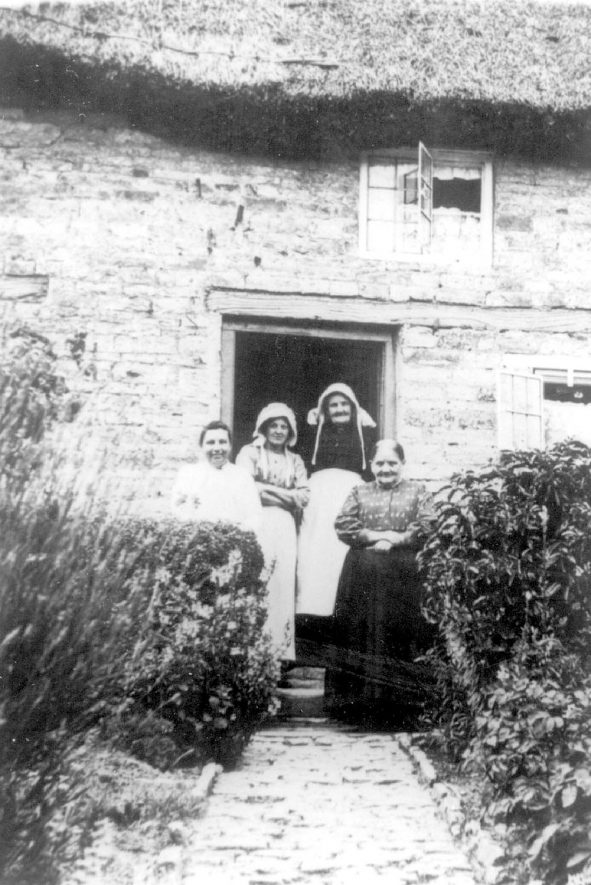 Group of four women standing at the doorway of a cottage in Lighthorne. 1900s[The