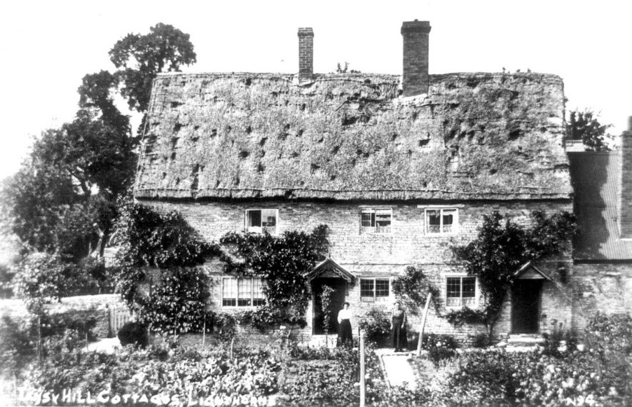 Tansy Hill Cottages, Lighthorne. A lady is seen standing in the doorway of these thatched cottages. 1900s[Originally the old, old school house]    IMAGE LOCATION: (Warwickshire Museums. Photographic Collections.)