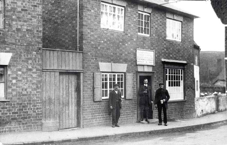 Hawten Duckett, the landlord's son, standing outside the public house with Cuckoo Chandler to the right and Randy French to the left, two characters of Kineton.  1908 |  IMAGE LOCATION: (Warwickshire Museums. Photographic Collections.) PEOPLE IN PHOTO: French, Randy, French as a surname, Duckett, Hawten, Duckett as a surname, Chandler, Cuckoo, Chandler as a surname