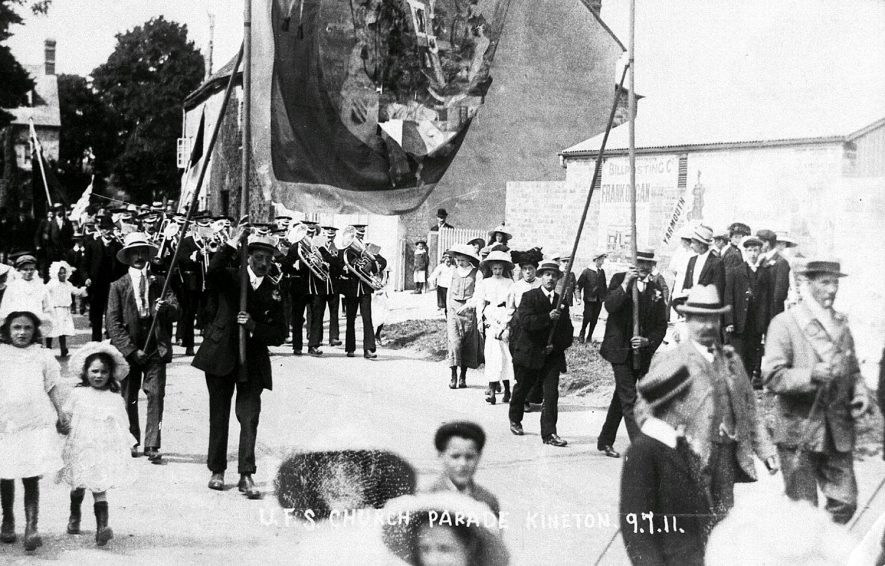 Oddfellows church parade, Kineton, led by Fenny Compton silver band. The banner bearers are C Mullins, J Mullins, William? and A Usher.  July 9th 1911 |  IMAGE LOCATION: (Warwickshire Museums. Photographic Collections.) PEOPLE IN PHOTO: Usher, A, Usher as a surname, Mullins, J, Mullins, C, Mullins as a surname