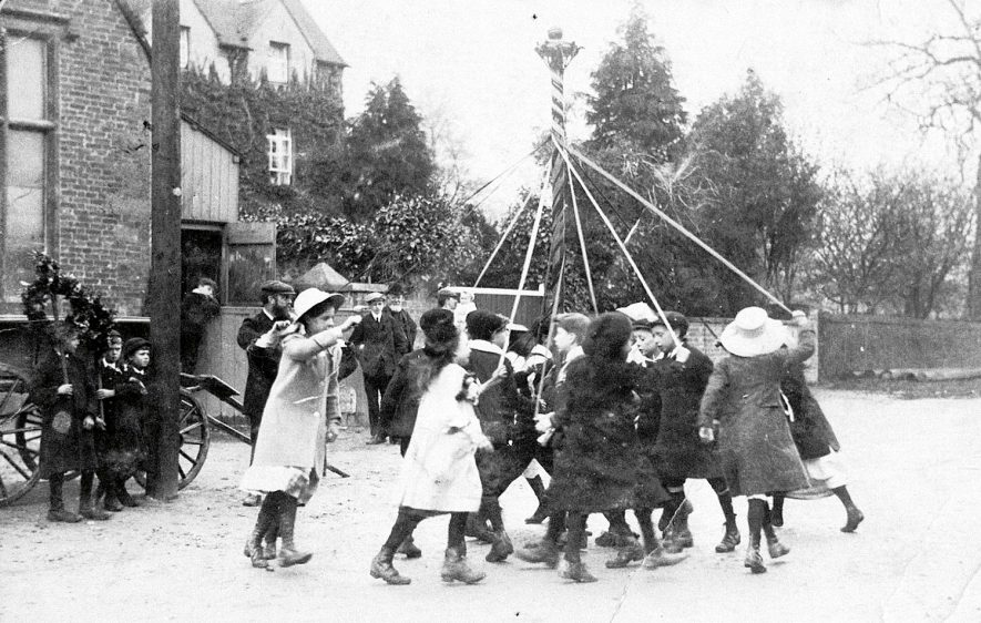 Children dancing round the maypole outside the church room in Southam Street, Kineton.  1908 |  IMAGE LOCATION: (Warwickshire Museums. Photographic Collections.)