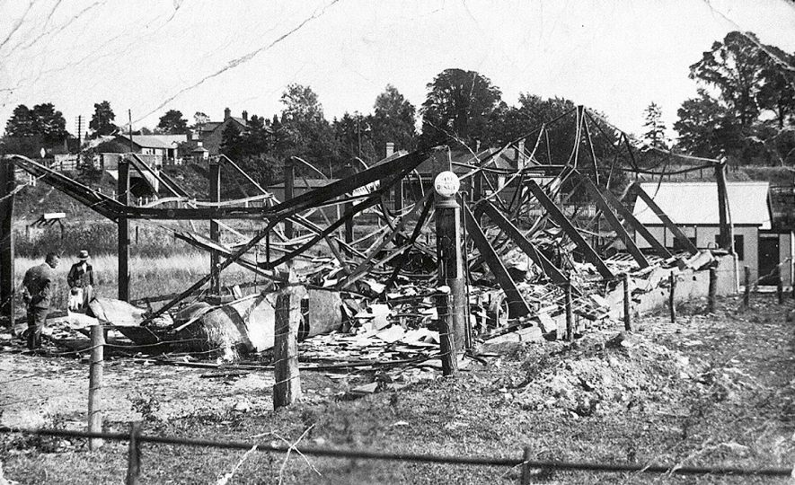 The remains of the Green Bus building and four buses after a fire, Kineton.  1933 |  IMAGE LOCATION: (Warwickshire Museums. Photographic Collections.)
