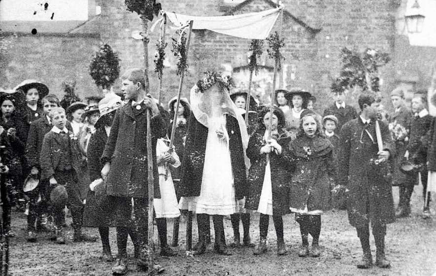 Children dressed up and carrying floral wands and canopy over ? May Queen. Kineton.  1909 |  IMAGE LOCATION: (Warwickshire Museums. Photographic Collections.)