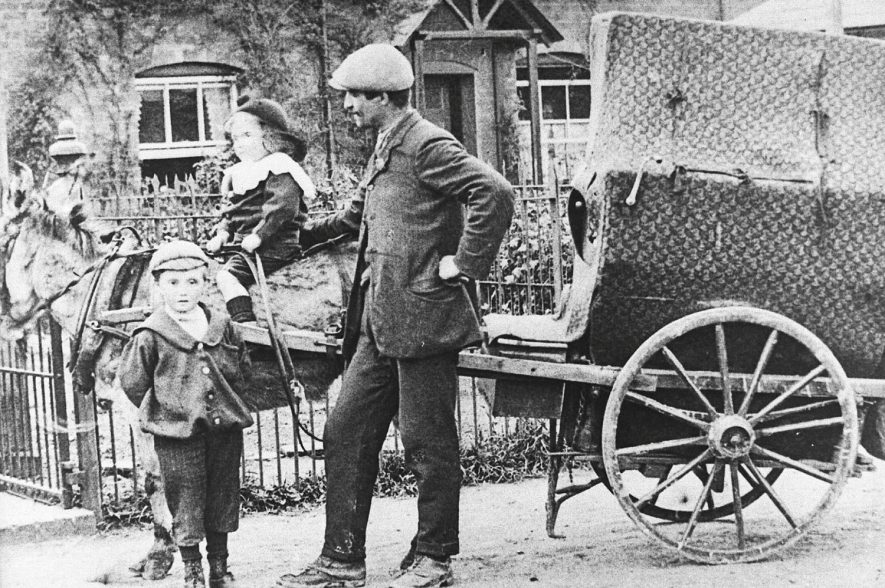 Italian organ grinder with a donkey and cart and two children posing with him, one on donkey in Alveston.  1908 |  IMAGE LOCATION: (Warwickshire Museums. Photographic Collections.)