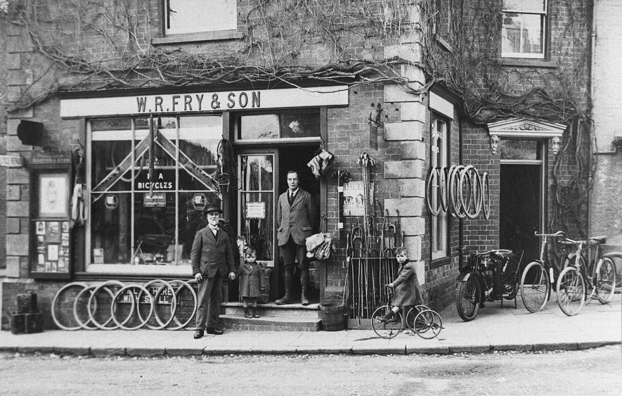 W.R. Fry & Son shop front, showing cycles and wheels on pavement, Shipston on Stour.  Standing outside, W.R. Fry, son Edgar Fry in doorway, grandsons Richard Edgar on tricycle and Sidney Trueman holding grandfather's hand.  1930s |  IMAGE LOCATION: (Warwickshire Museums. Photographic Collections.) PEOPLE IN PHOTO: Fry, W R, Fry, Richard Edgar, Fry, Sidney Trueman, Fry, Edgar, Fry as a surname