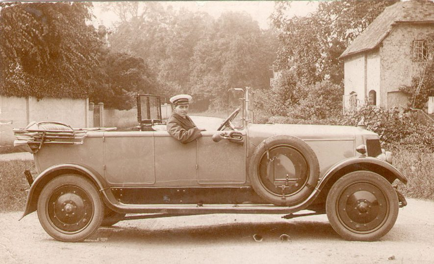 An Armstrong Siddely car standing in street with a chauffeur in the driving seat at Alveston.  1900s |  IMAGE LOCATION: (Warwickshire Museums. Photographic Collections.)