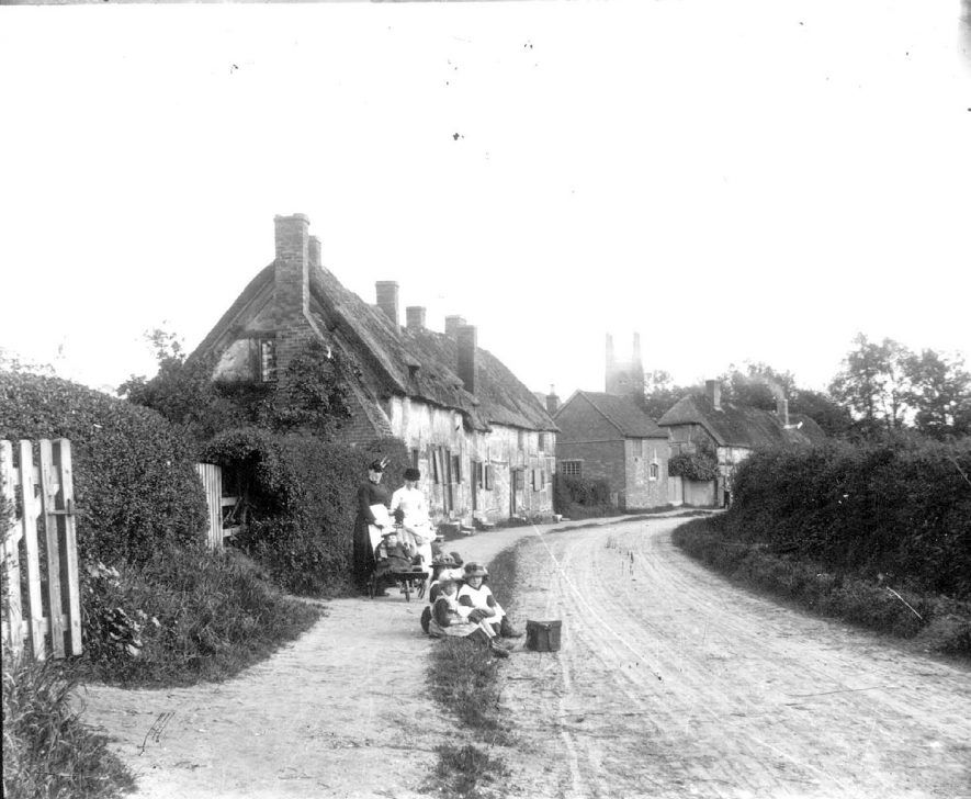 Village street with cottages, Hampton Lucy.  Children sitting by lane.  Two  women with perambulator.  1900s |  IMAGE LOCATION: (Warwickshire Museums. Photographic Collections.)