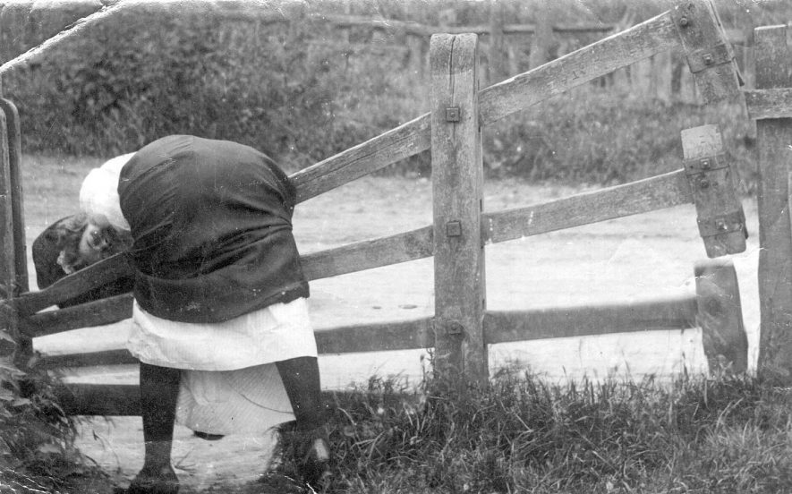 Girl leaning over tumbledown stile.  Photograph has