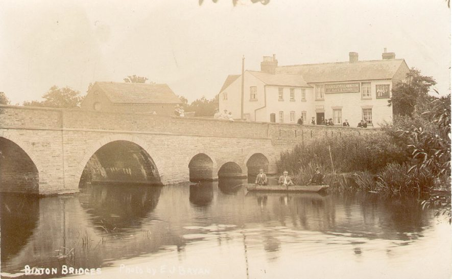Binton Bridges, spanning three channels of River Avon.  Public House on far bank.  Anglers in boat and onlookers on bridge.  1900s |  IMAGE LOCATION: (Warwickshire Museums. Photographic Collections.)