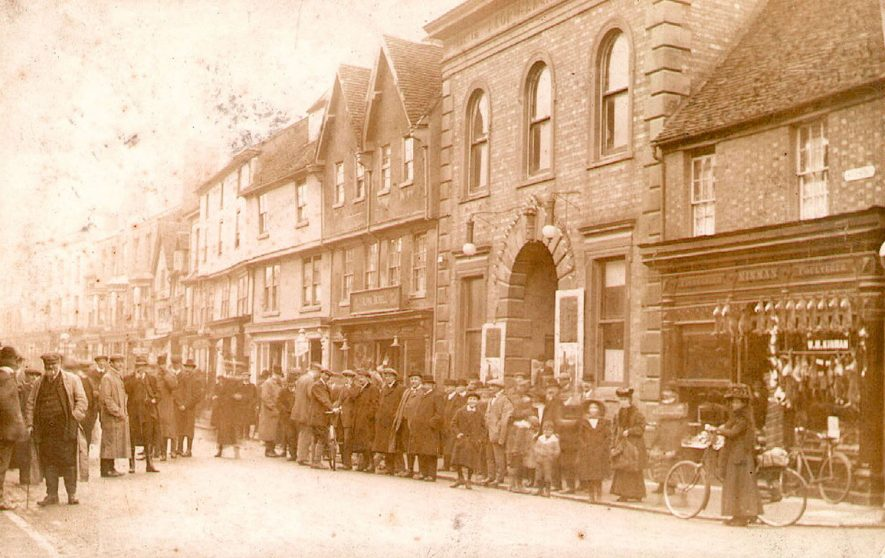 A group of men, women and children standing in High Street, Stratford upon Avon. Kinman's fishmonger and poulterer's shop is seen in the foreground.  1910s |  IMAGE LOCATION: (Warwickshire Museums. Photographic Collections.)