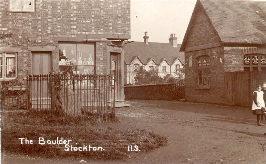 A large boulder, surrounded by iron railings and a shop behind, Stockton.  1900s |  IMAGE LOCATION: (Warwickshire Museums. Photographic Collections.)