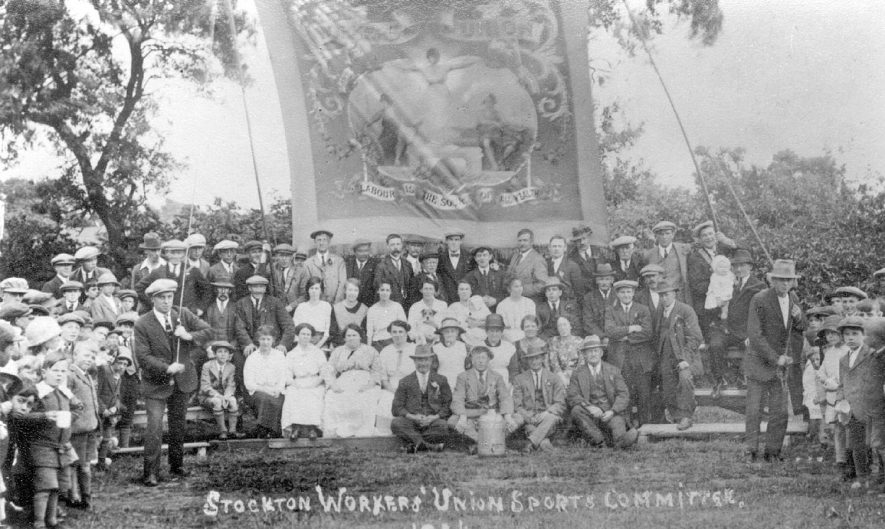 Group of men and women carrying a large banner from the Stockton Workers' Union sports committee. They are watched by children and others.  1924 |  IMAGE LOCATION: (Warwickshire Museums. Photographic Collections.)