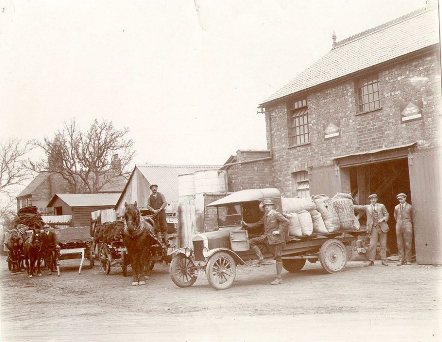 View of Kendall's merchants yard, Stockton.  A lorry is loaded with animal feed and horses and carts with coal. Workers are also pictured.  1920s |  IMAGE LOCATION: (Warwickshire Museums. Photographic Collections.)