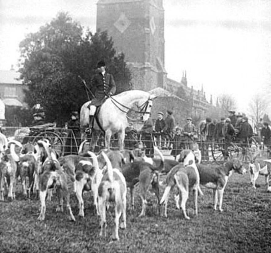 The meet of the Warwick Hunt at Brailes Church with hounds and huntsmen and onlookers.  1910s |  IMAGE LOCATION: (Warwickshire County Record Office)
