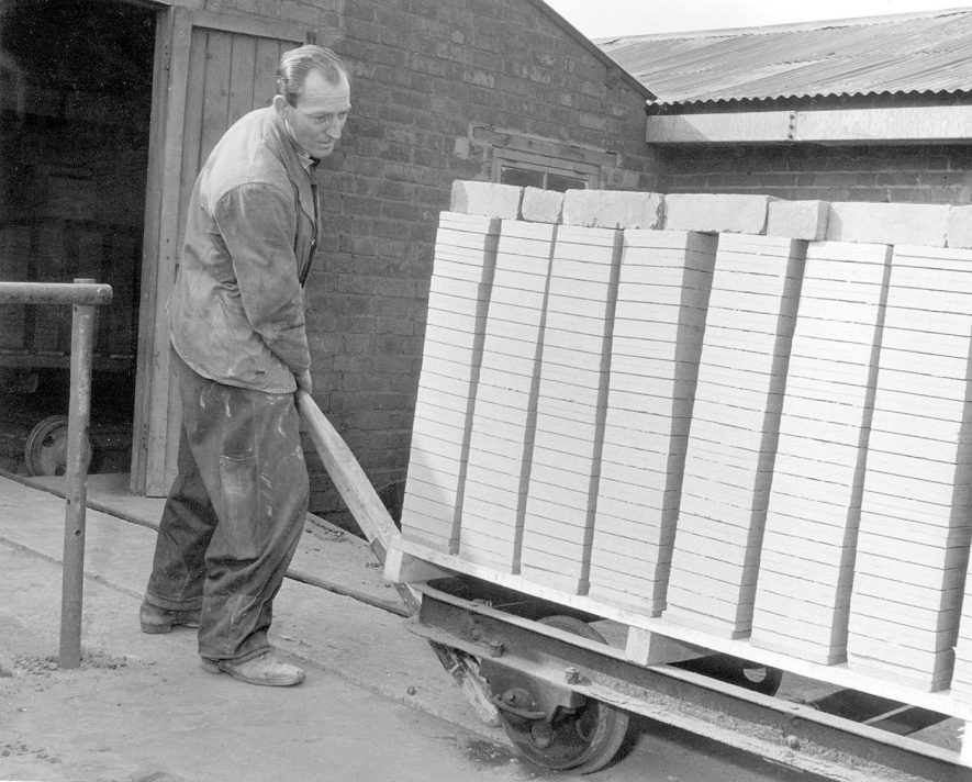 'Green' tiles being pushed from the dry sheds on the left, to the kilns, at the clay pits, Napton on the Hill.  1950s