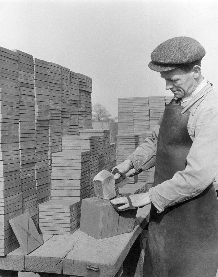 Sorting and inspecting the fired tiles, knocking them apart and rejecting waste (tile with X is the standard). The job was done in the open air as good lighting was necessary.  Napton on the Hill.  1950s    IMAGE LOCATION: (Warwickshire Museums. Photographic Collections.)