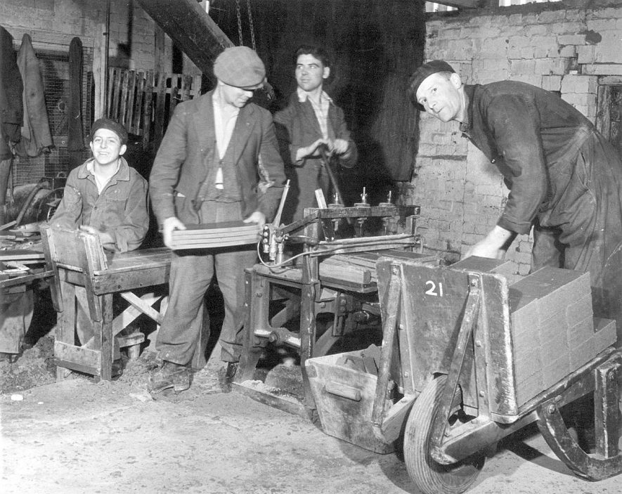 Workers in the tile kilns, Napton on the Hill. On the left a continuous strip of clay is cut into lengths. It is then carried to the cutting machine (man with 4in hand). The cutting machine then cuts them into 'bats' which are being piled into barrow.  1950s [The person loading the tiles onto the barrow is Jack Rowberry.] |  IMAGE LOCATION: (Warwickshire Museums. Photographic Collections.)
