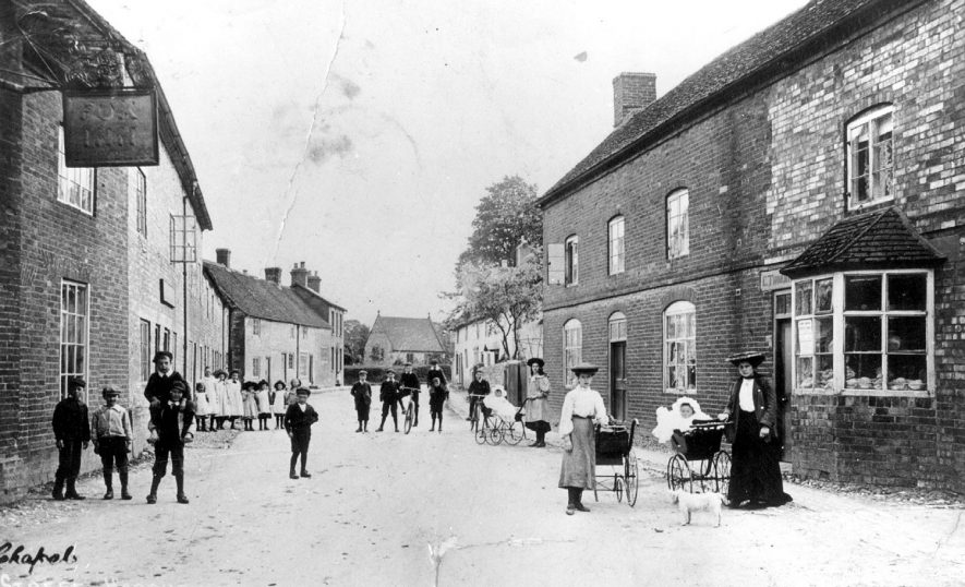 Women with perambulators and children standing in Chapel Street, Harbury. The Fox Inn is seen in the left foreground. 1907[The building behind the two ladies with prams was the old bakery and the shop attached is where the bread baked in the bakery was sold] |  IMAGE LOCATION: (Warwickshire Museums. Photographic Collections.) PEOPLE IN PHOTO: Dickins, Mr