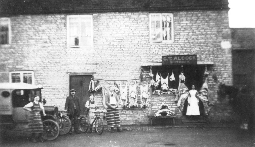 G T Alcock's butchers shop in Harbury. Carcasses are seen hanging on the outside wall and a delivery van and boy with cycle are also in the picture.  1900s |  IMAGE LOCATION: (Warwickshire Museums. Photographic Collections.) PEOPLE IN PHOTO: Dickins, Mr, Dickins as a surname