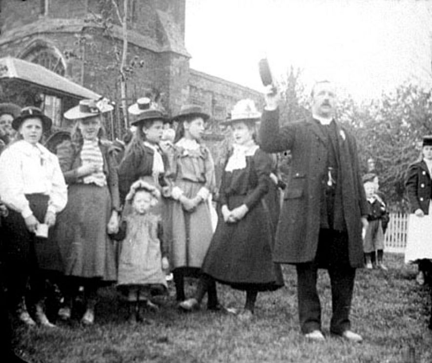 Celebration of  Mafeking Day outside the church in Lower Brailes. The Vicar calls for three cheers for the Queen.  1900 |  IMAGE LOCATION: (Warwickshire County Record Office)