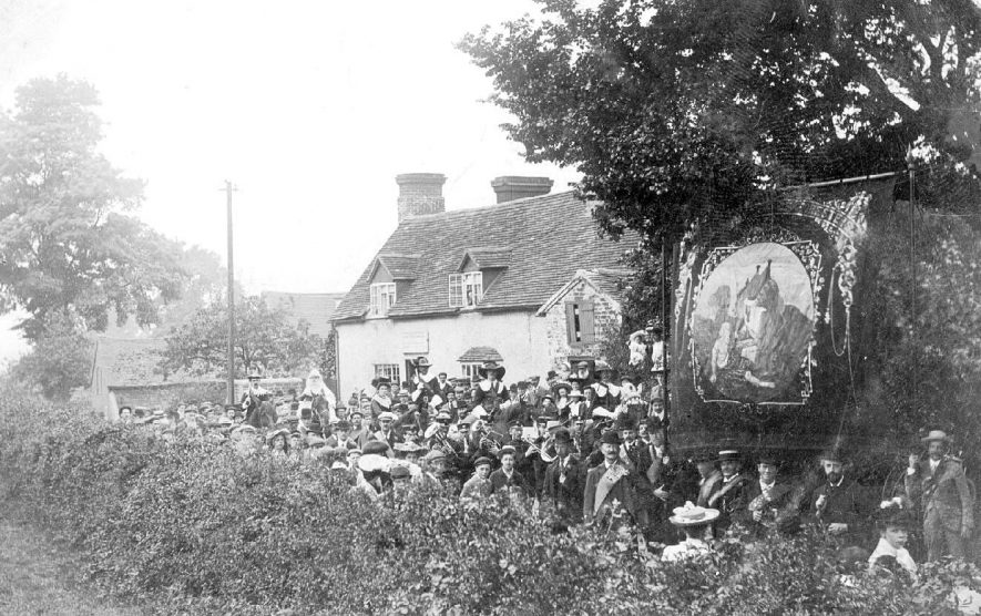 The Crown Public House, Claverdon, and crowd with banner. ? Friendly society.  1900s |  IMAGE LOCATION: (Warwickshire County Record Office)