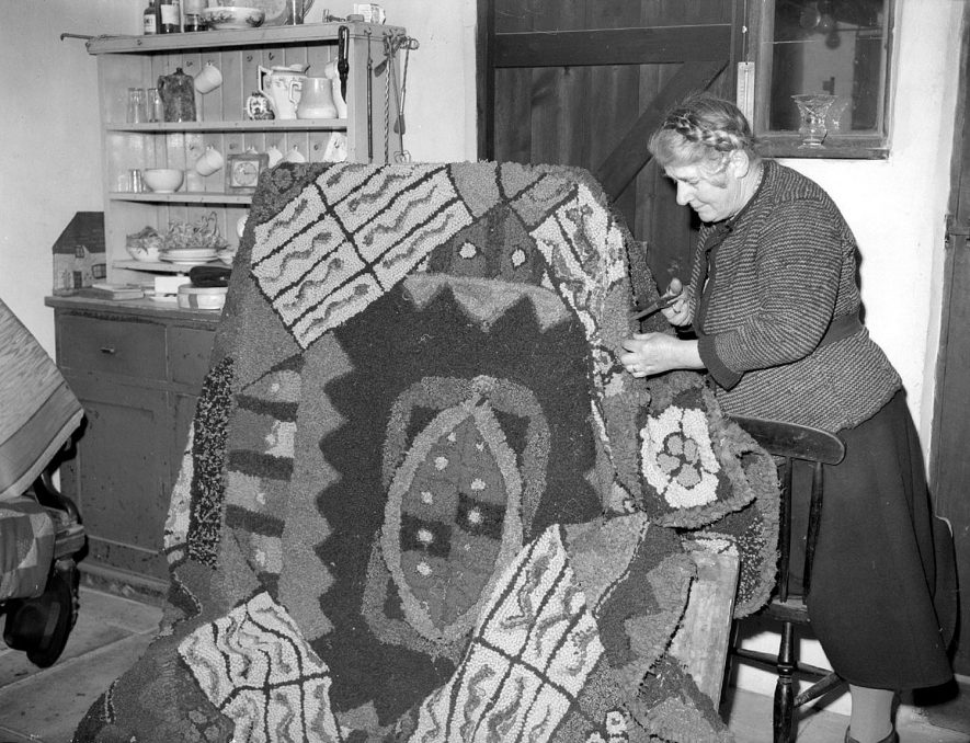 Mrs Emerson and her rug at Old Town Farm, Bishop's Itchington. February 15th 1955[The electoral register for 1955 show that an Ada and John Emerson were in fact living at Brookside Holding, Bishops itchington and not at Old Town Farm] |  IMAGE LOCATION: (Warwickshire County Record Office) PEOPLE IN PHOTO: Emerson, Mrs, Emerson as a surname