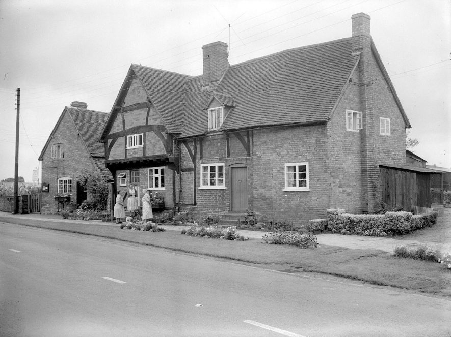Bretford, best kept village. Mrs F.A. White, Mrs E.A. Cooper and Mrs I.E. Halfpenny and flower beds outside the Old Oaks.  August 1958 |  IMAGE LOCATION: (Warwickshire County Record Office) PEOPLE IN PHOTO: White, Mrs F A, White as a surname, Halfpenny, Mrs I E, Halfpenny as a surname, Cooper, Mrs E A, Cooper as a surname
