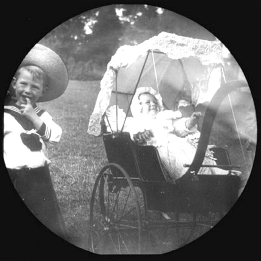 Infant, Joan Buckingham in a pram accompanied by a little boy in a sailor suit. Lower Brailes.  1900s |  IMAGE LOCATION: (Warwickshire County Record Office) PEOPLE IN PHOTO: Buckingham, Joan, Buckingham as a surname