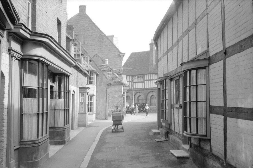 Shops in  Butter Street, showing a woman pushing a pram and the Old butter market beyond the street, Alcester.  1950s |  IMAGE LOCATION: (Warwickshire County Record Office)