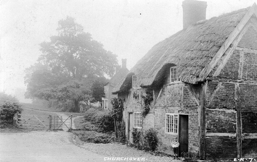 Timbered and thatched cottage by gate leading to footpath, a further house is beyond the gate, Churchover.  1900s |  IMAGE LOCATION: (Warwickshire County Record Office)