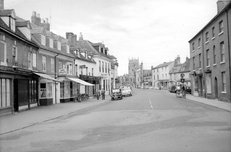 Alcester High Street, showing shops, cars and church tower.  1950s |  IMAGE LOCATION: (Warwickshire County Record Office)