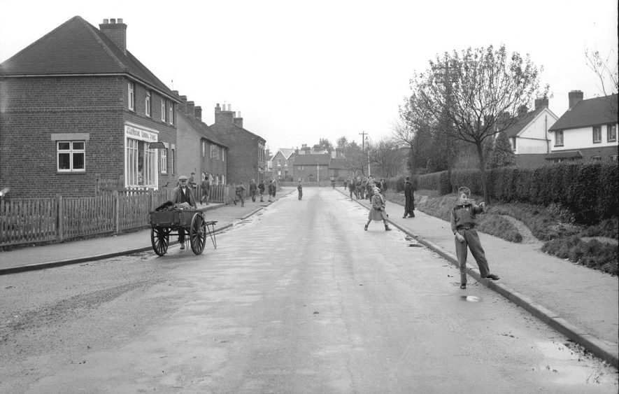 School Road, Alcester, showing houses, a shop front, a man with a hand cart and children walking on the road and pavement.  1950s |  IMAGE LOCATION: (Warwickshire County Record Office)