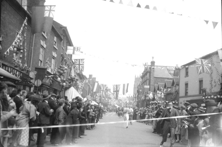 Street with school and shops, decorated with bunting for Coronation celebration.  Crowd watching men racing in the street, Alcester.  1953 |  IMAGE LOCATION: (Warwickshire County Record Office)