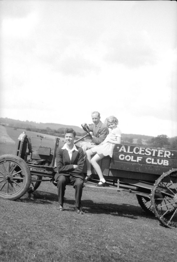 Grass-cutting vehicle on Alcester golf course.  Two men and girl seated on it.  1950s |  IMAGE LOCATION: (Warwickshire County Record Office)