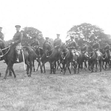 Warwick.  Troop of mounted cavalry in a park