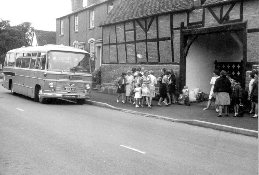 The Malt House, Bridge Street, Barford. A coach is approaching and a group of children (some are in girl guide uniform) and adults are standing on the pavement.  1967 |  IMAGE LOCATION: (Warwickshire County Record Office)
