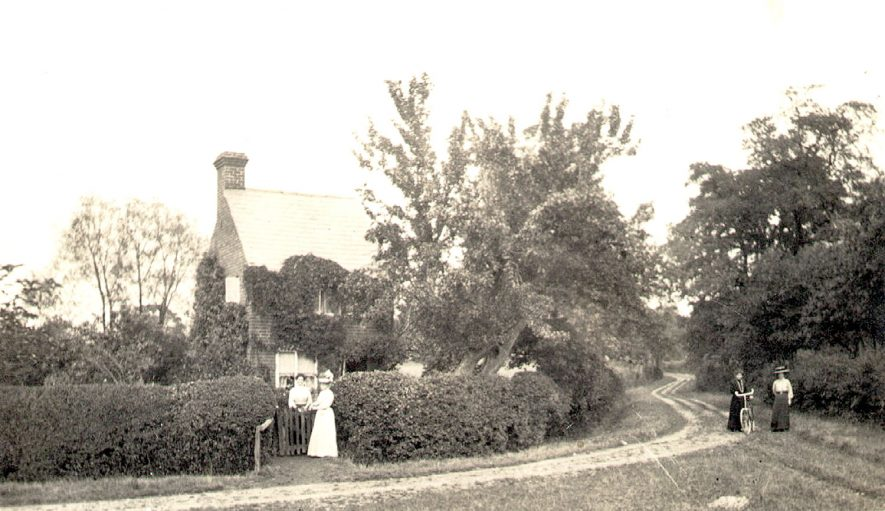 Buckley Green, Beaudesert.  Cottage with man and woman at gate.  Two women with bicycle in lane.  1912 |  IMAGE LOCATION: (Warwickshire County Record Office)