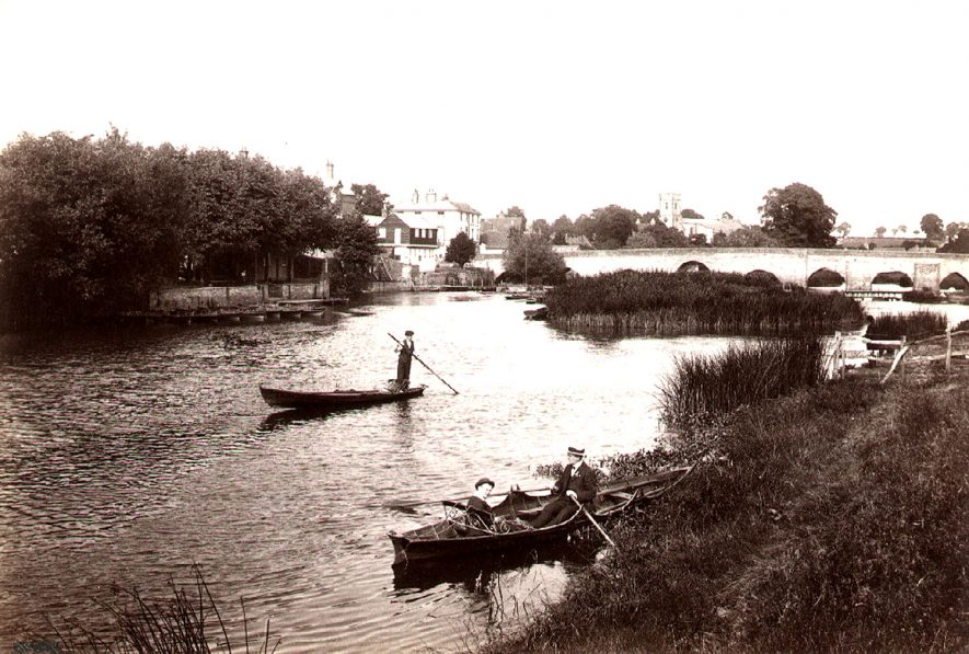 Church, White Lion public house and bridge from down river, Bidford on Avon.  Two small boats with people in them.  1910s |  IMAGE LOCATION: (Warwickshire County Record Office)