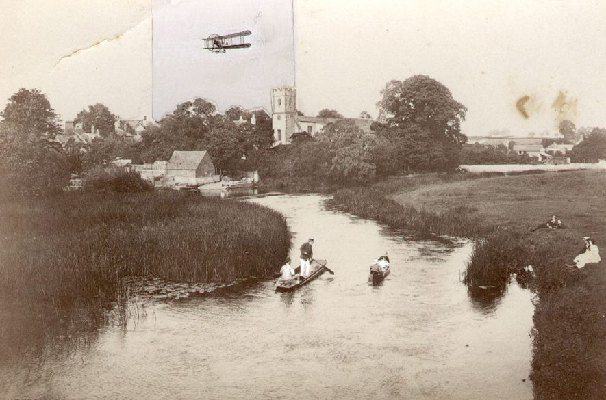 View of Bidford on Avon church from bridge. People punting on the River Avon and walking on bank.  Inserted cut-out of bi-plane.  1910 |  IMAGE LOCATION: (Warwickshire County Record Office)
