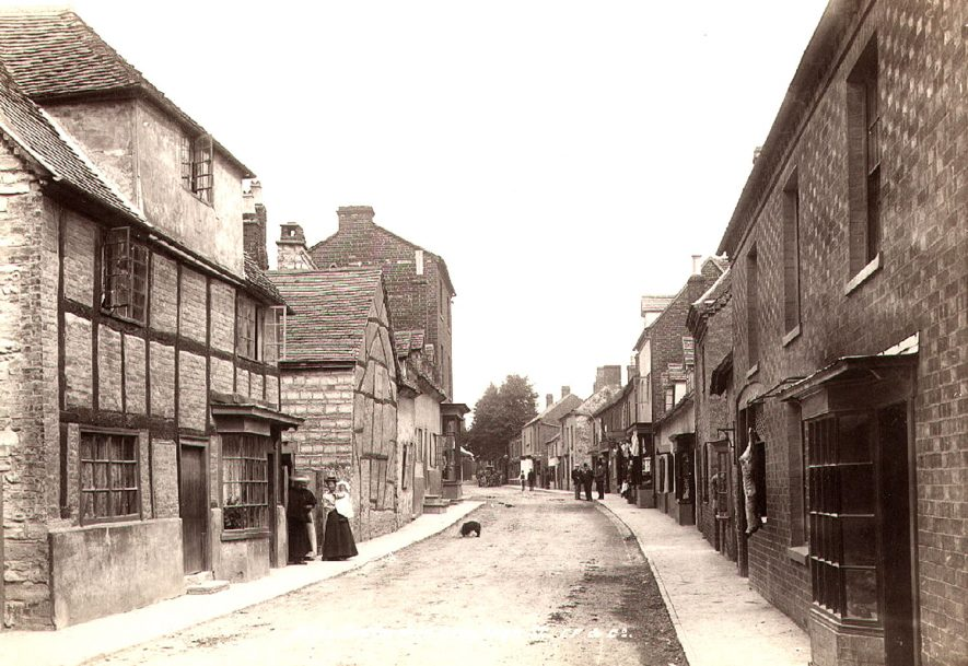 High Street, Bidford on Avon, looking east from White Lion public house.  1899[On the right - hand side is a carcass of meat outside a butcher's shop, which was established in 1840, at one time owned and run by Mr. George Winnett. It was taken over by Mr. Charles Hunt in the early 1930's, followed by his son Rowland Hunt until the shop closed in 1970.The shop became part of the adjoining White Lion Hotel, the metal meat hanging rail remains to this day.] |  IMAGE LOCATION: (Warwickshire County Record Office)