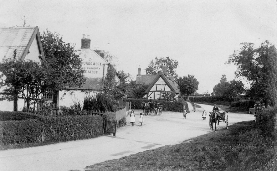 Bubbenhall village street with cottages and the Three Horseshoes public house. Two horses and traps.  Children playing in street.  1900s |  IMAGE LOCATION: (Warwickshire County Record Office)