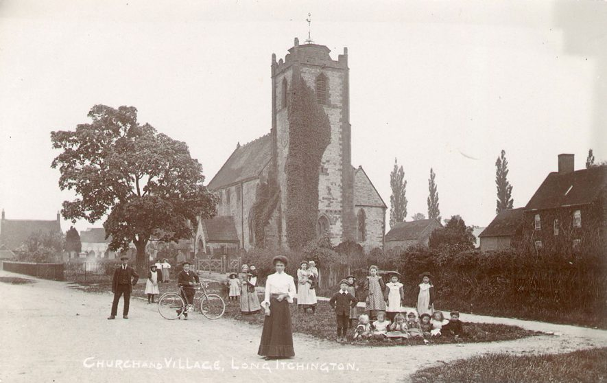 Long Itchington Parish Church, with a man and woman in street with group of children.  Boy with decorated bicycle.  1900s |  IMAGE LOCATION: (Warwickshire County Record Office)
