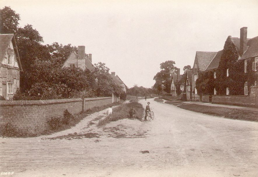 The main village street in Barton. Two boys with a bicycle and a dog are seen in the foreground.  Circa 1910 |  IMAGE LOCATION: (Warwickshire County Record Office)
