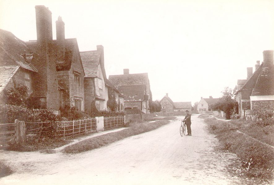 The main street in Barton, looking west. A man and his bicycle are seen standing in the road.  Circa 1910 |  IMAGE LOCATION: (Warwickshire County Record Office)