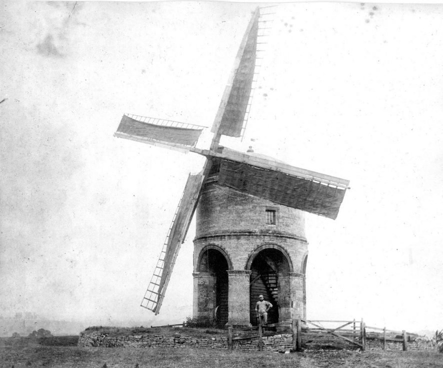 Chesterton Windmill with man posing outside. c.1930sUnique stone tower built for Sir Edward Peyto, ('EP 1632' on cap).Major restorations 1776 and 1860. Ceased work 1910. Sails repaired and altered 1930 and later.. Restored 1965-71 by Warwick County Council, Department for the Environment and the Society for the Protection of Ancient Buildings and others under the direction of D. Ogden.36ft (c.11m) high, 22ft 9ins (c.7m)diameter, two storey tower of cylindrical body (with windows) set on six semicrcular arches on piers, aluminum covered dome cap, 4 common sails and complete with all machinery and 2 pairs stones. |  IMAGE LOCATION: (Warwickshire County Record Office)